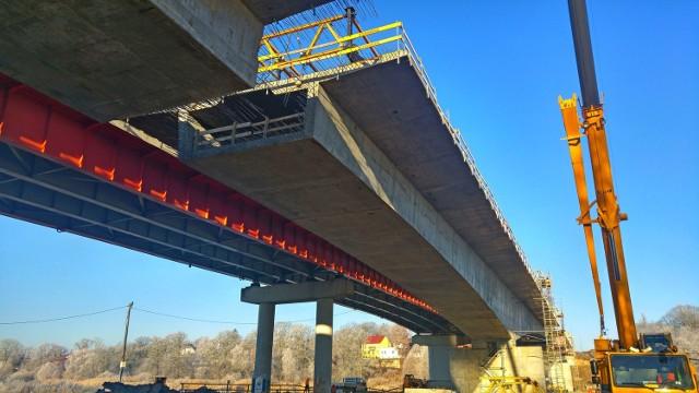 Trasa S3 w Lubuskiem to teraz w wielu miejscach ogromny plac budowy. Trwa m.in. budowa odcinka z Sulechowa do Nowej Soli. W ramach tej inwestycji powstaje nowy most na Odrze w Cigacicach. Odcinek trasy S3 między Sulechowem, a Nową Solą podzielono na trzy fragmenty. Pierwszy z nich to odcinek z Sulechowa do węzła Zielona Góra Północ. Ma on 13,4 km długości, a oddanie do użytku planowane jest w sierpniu 2017 r. Koszt realizacji tej inwestycji to 299 mln zł. Zobacz też:  Budowa S3 w Lubuskiem. Kiedy pojedziemy nad morze bez stania w korkach?W ramach budowy tego fragmentu lubuskiej ekspresówki powstaje też zupełnie nowy most na Odrze w Cigaciach. - Przeprawa jest budowana z dwóch stron rzeki i jest już niemalże połączona - mówi Anna Jakubowska z zielonogórskiego oddziału Generalnej Dyrekcji Dróg Krajowych i Autostrad. Ale most, którego ukończenie zaplanowano na sierpień 2017 r., powstaje tylko na dwóch pasach jezdni. Po jego otwarciu stara przeprawa, którą ruch odbywa się obecnie, zostanie zburzona, a w jej miejsce będzie budowana nowa. Zakończenie prac zaplanowano na 2019 r. Wtedy kierowcy będą mogli korzystać z dwóch, równoległych do siebie mostów na Odrze. Do 2019 r. ruch na S3 na wysokości Cigacic będzie się odbywał jednym mostem, więc będzie tu wąskie gardło. W trakcie budowy jest odcinek S3 od węzła Zielona Góra Północ do Niedoradza. Ma on długość 13,3 km, a jego otwarcie zaplanowano na maj 2018 r. Koszt inwestycji oszacowano na 194 mln zł.Trzeci budowanych z fragmentów to Niedoradz - Nowa Sól. Ma on długość 17,3 km i ma zostać zakończony w lipcu 2018 r. Koszt inwestycji to 188 mln zł. Przypomnijmy, że trwa też budowa drugiej nitki obwodnicy Gorzowa Wlkp. Zakończenie prac zaplanowano na kwiecień 2017 r. Inwestycja pochłonie 289 mln zł, za te pieniądze powstanie 11,6 km nowej drogi. Zakończono już budowę drugiej nitki obwodnicy Międzyrzecza. Ma ona długość 6,4 km, a jej budowa kosztowała 102 mln zł. Zobacz też:  Prace przy budowie S3 w Lubuskiem [ZDJĘCIA]
