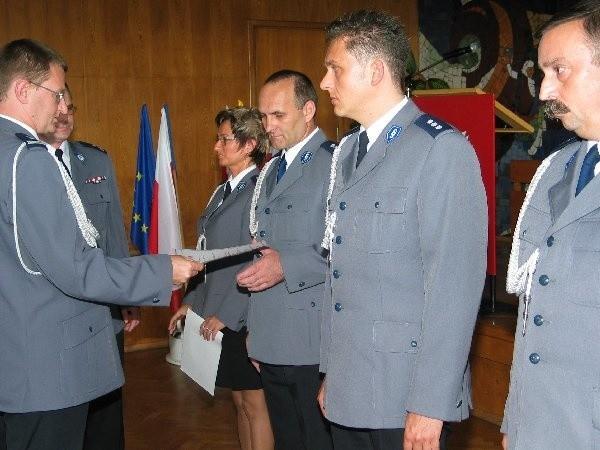 Mł. insp. Adam Gotowicz, zastępca komendanta  wojewódzkiego policji wręcza grudziądzkim  funkcjonariuszom nominacje na wyższe stopnie  służbowe.
