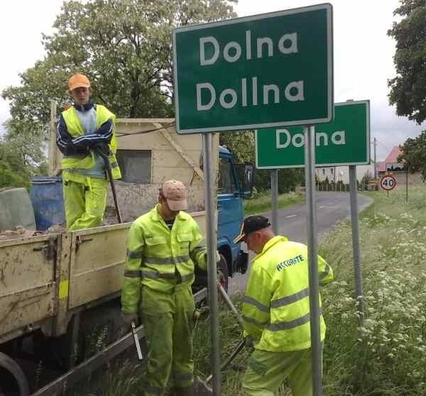 Znaki w języku polskim i niemieckim ustawione przy wjeździe do miejscowości.
