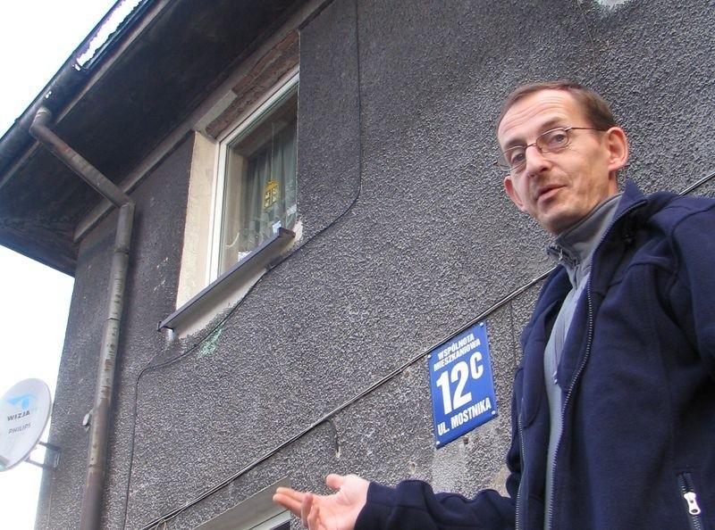 Bogdan Bulczak pokazuje skorodowaną rynnę i porośnięty mchem dach.