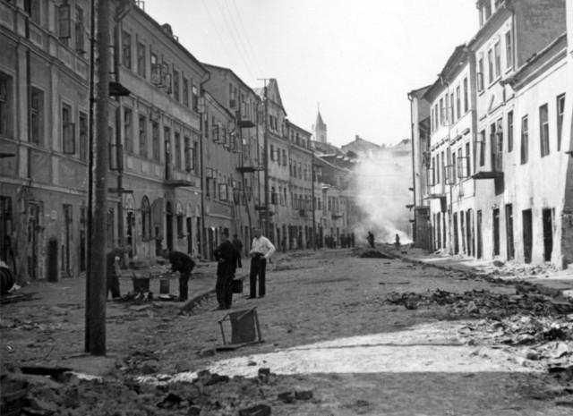 Wyburzanie, dziś nieistniejącej, ulicy Szerokiej, w tle kurz z rozbieranych kamienic z ul. Kowalskiej.