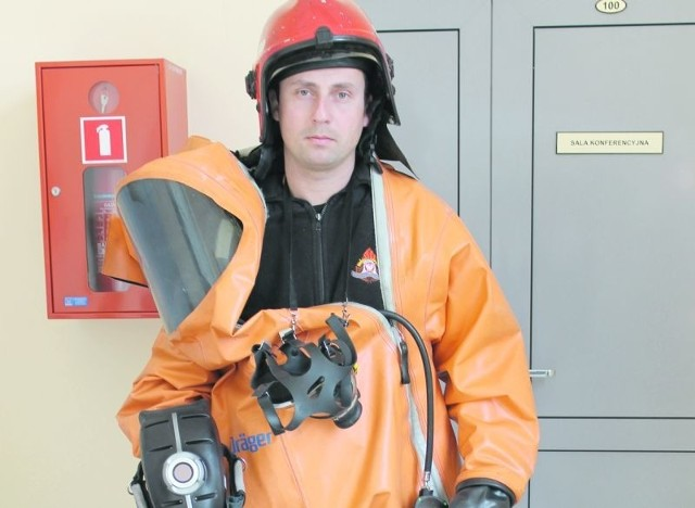Starszy sekcyjny Michał Gołębiewski pokazuje pożyczony kombinezon do ratownictwa chemicznego, jakiego brakuje żagańskiej straży pożarnej