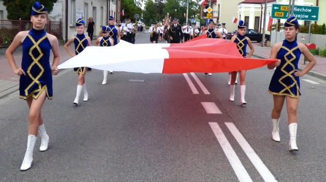 """Uroczysty przemarsz ulicami Skalbmierza otwierały mażoretki, niosąc wielką, 15-metrowej długości """"biało-czerwoną""""."""