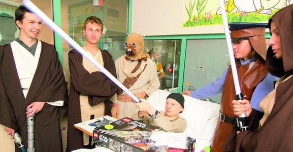"""Bohaterowie """"Gwiezdnych wojen"""" odwiedzili Jasia w bydgoskim szpitalu. Chłopiec nie odmówił sobie wypróbowania świetlnego miecza."""