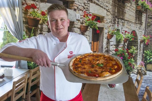 Właściciel Michał Gotkowicz prezentuje tradycyjną włoską pizzę. Lokal znajduje się przy ulicy Żwirki i Wigury 33 w Radomiu.