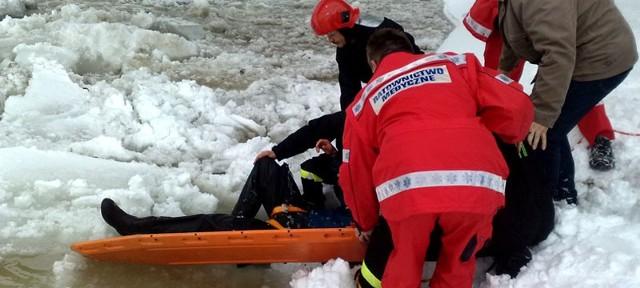 Ratownicy udzielają pomocy rannemu wędkarzowi.