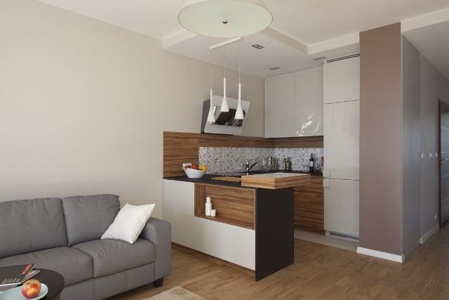 Kuchnia otwarta na salonKuchnia otwarta na pokój dzienny to układ spotykany nie tylko w nowoczesnych domach jednorodzinnych, ale również w małych mieszkaniach w blokach. Otwarta przestrzeń sprzyja życiu rodzinnemu. A dzięki zmniejszeniu liczby ścian działowych nawet małe mieszkanie zyskuje na przestronności. Granicą umowną między strefą do wypoczynku a kuchnią jest najczęściej stół kuchenny, wysoki barek lub wyspa kuchenna.