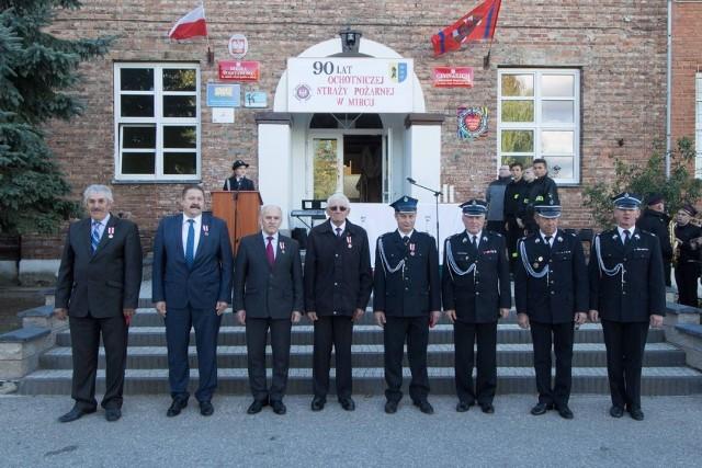 """Odznaczeni wszystkimi medalami """"Za zasługi dla pożarnictwa"""" i odznaczający ich (z prawej) na pamiątkowym zdjęciu."""