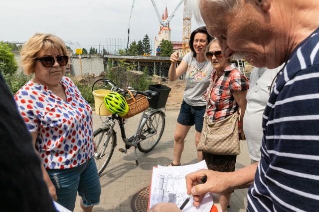 Mieszkańcy pokazują projekt, na którym widać, gdzie mają stanąć dwa kolejne bloki.