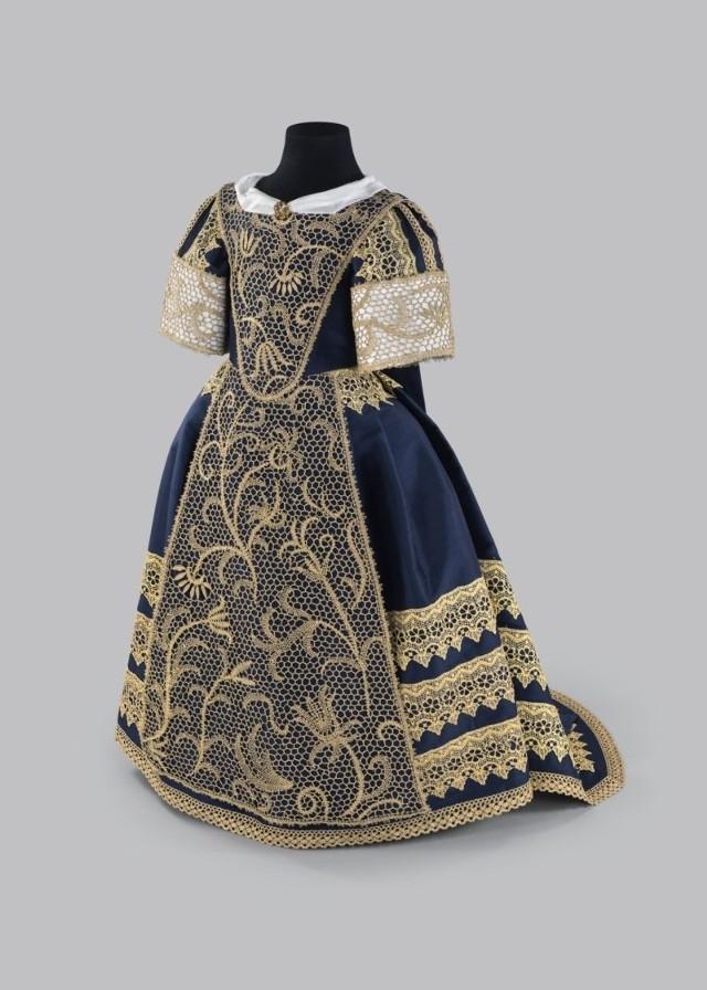 Widoczną na fotografii rekonstrukcję stroju dziecięcego z minionej epoki wykonał Marek Ziętek.