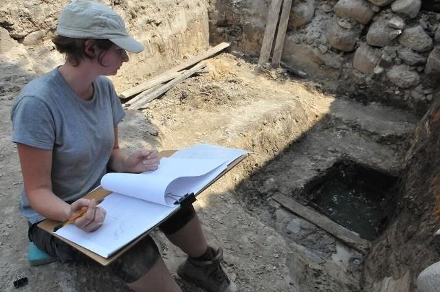 Aleksandra Augustyniak opisuje znaleziska. Obok niej średniowieczny dół kloaczny z zachowaną drewnianą obudową i grubą warstwą gliny, pełniącej funkcję izolacyjną.