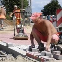 Kamil Kożuchowski i jego koledzy pomimo upalnych dni pracują przy budowie chodników przy ulicy Sikorskiego.