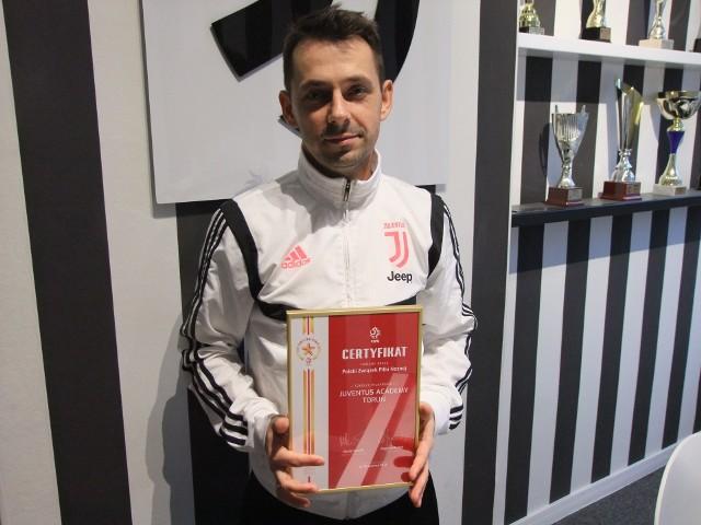 Paweł Kędzierski, dyrektor Juventus Academy Toruń, prezentuje certyfikat