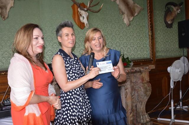 Przedstawicielki Balu Polskiego: Marlena Anderson (od lewej) i Dorota Sztorc oraz Alicja Krukowska, kierownik opolskiego ośrodka PZG podczas uroczystego przekazania czeku.