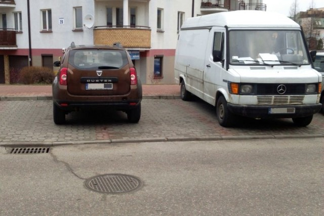 Dacia Duster chamsko zaparkowana pośrodku dwóch miejsc.