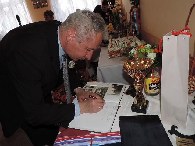 Senator Piotr Gruszczyński wpisuje się do księgi pamiątkowej