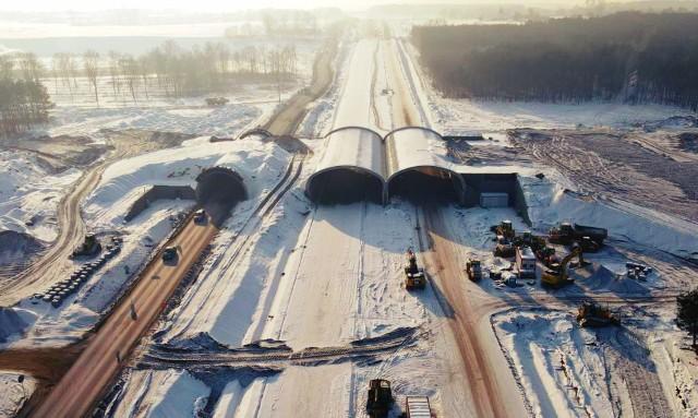 Zaglądamy na budowę trasy S5 na odcinku Białe Błota - Szubin w woj. kujawsko-pomorskim. Dzięki zdjęciom opublikowanym przez Generalną Dyrekcję Dróg Krajowych i Autostrad możemy zobaczyć, jak budowa prezentuje się w zimowej scenerii.  Zdjęcia z drona można obejrzeć w galerii.   Przesuń zdjęcie gestem lub naciśnij strzałkę w prawo   Odcinek liczy 9,7 km. Wartość kontraktu to blisko 360 mln zł.