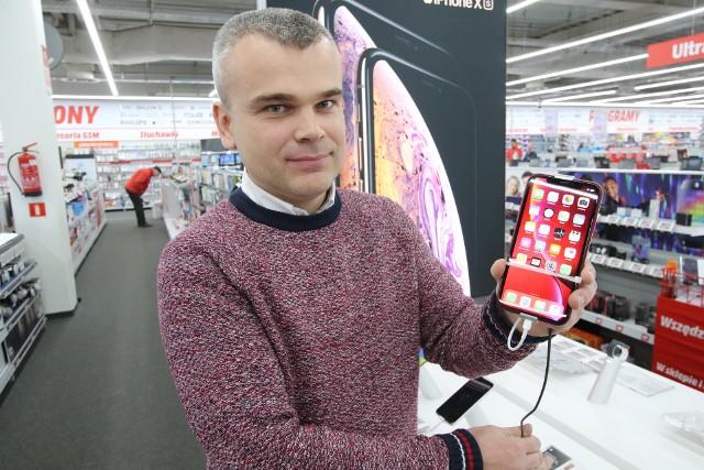 W Media Markt Cyber Monday to przedłużenie promocji. Na zdjęciu kierownik Marek Marszałek z przecenionym Iphone'em 7.