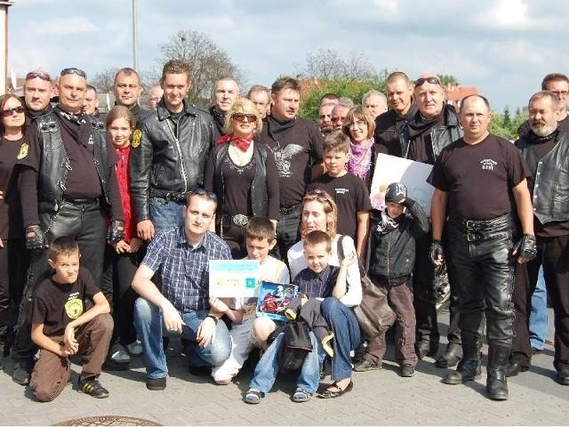 Pamiątkowe zdjęcie na parkingu. 5-letni Paweł chory na mukowiscydozę z rodzicami i braćmi  w otoczeniu darczyńców