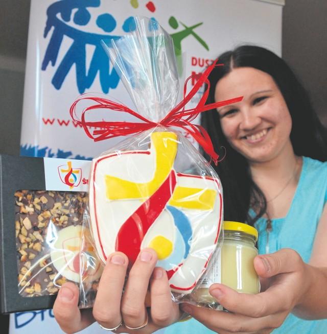 Agnieszka Popardowska z diecezjalnego centrum ŚDM prezentuje smakołyki, jakie można nabyć i wesprzeć wydarzenie