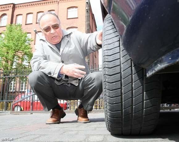 Eugeniusz Szydłowski obok samochodu, którym wjechał w roztopiony asfalt