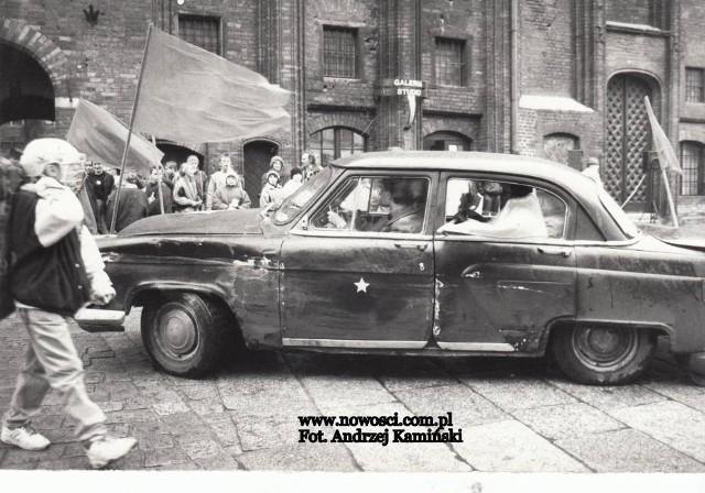"""Zapraszamy na przejażdżkę po Toruniu sprzed lat i przegląd pojazdów, jakie w tamtych czasach przetaczały się po ulicach miasta. Produkowanych seryjnie i tych niepowtarzalnych, jakie można było zobaczyć tylko w Toruniu. Czarna wołga przed toruńskim Ratuszem Staromiejskim. Ucharakteryzowana, ponieważ pojazd wziął w 1992 roku udział w inscenizacji, jaką redakcje """"Nowości"""" oraz """"Radia Toruń"""" przygotowały """"z okazji"""" 75 rocznicy rewolucji październikowej.  WIĘCEJ NA KOLEJNCYH STRONACH >>>"""
