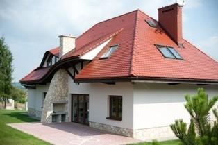 Dom z zewnątrz z widocznymi oknami fasadowymi i dachowymiZakup okien: komfort termiczny i ekstrawagancki wygląd stolarki okiennej