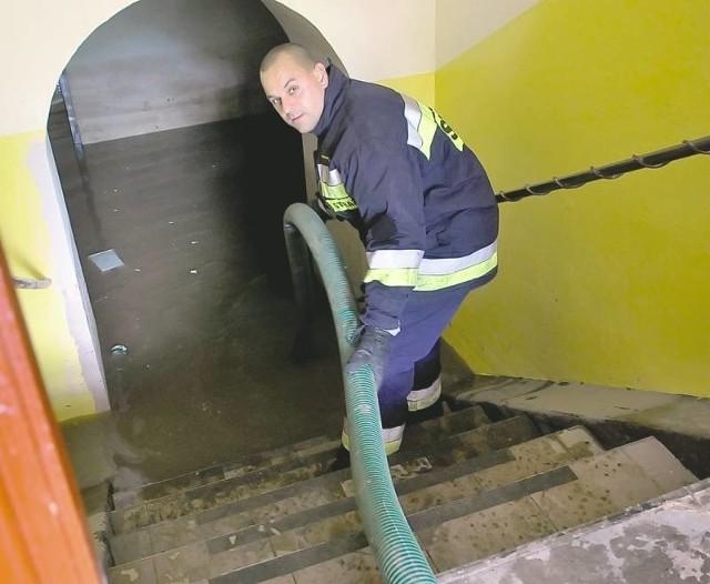 Marcin Kasprzak uruchamia pompę, dzięki której będzie można pozbyć się wody ze szkolnej stołówki