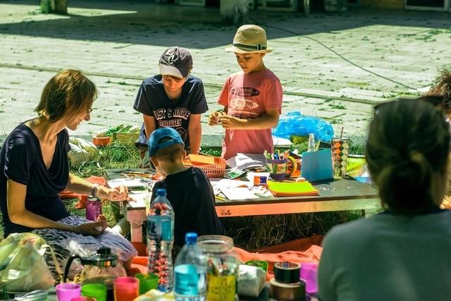 """Głównym celem warsztatów """"Zabawki z trawki"""" będzie przedstawienie dzieciom roślin najczęściej spotykanych w mieście oraz dawnego wykorzystania ich właściwości – szczególnie tych przydatnych do zabaw na świeżym powietrzu. Ponadto maluchy spróbują również stworzyć zabawki z rzeczy odnalezionych pod drzewami, wśród kwiatów i na chodnikach, by później pofarbować je naturalnymi barwnikami własnej roboty."""
