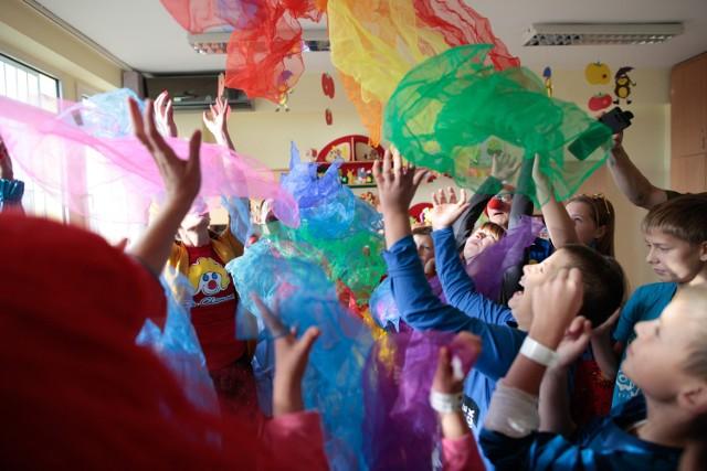 """Wolontariusze Fundacji """"Dr Clown"""" przekazali trzem opolskim szpitalom wesołe Hop-Gry do popularnej gry w klasy.  To element programu terapii śmiechem i zabawą, prowadzonego przez Fundację """"Dr Clown"""" od 1999 roku."""