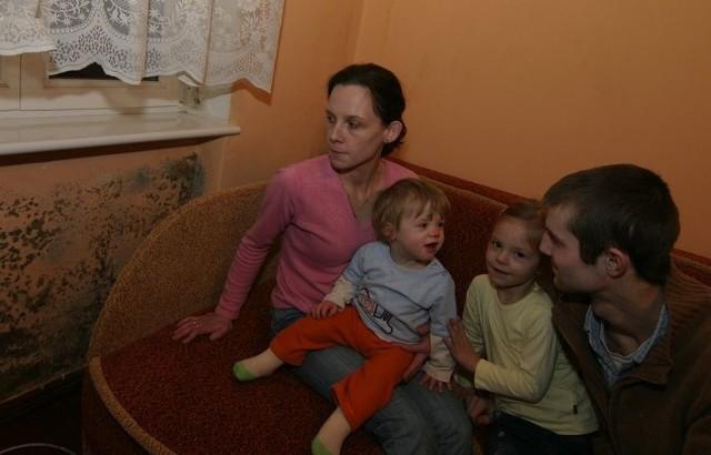 Państwo Gołębiewscy z córkami przy zagrzybiałej ścianie.