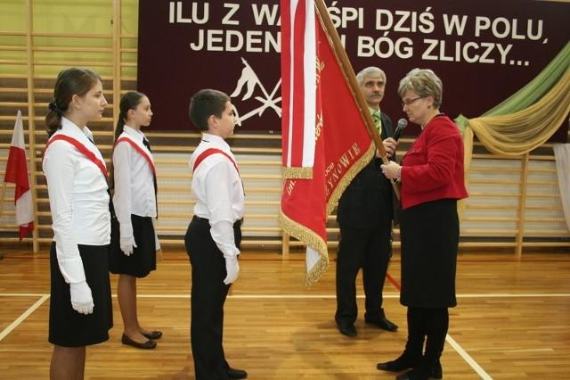 Dyrektor szkoły, JOlanta Dawid przekazuje sztandar uczniom