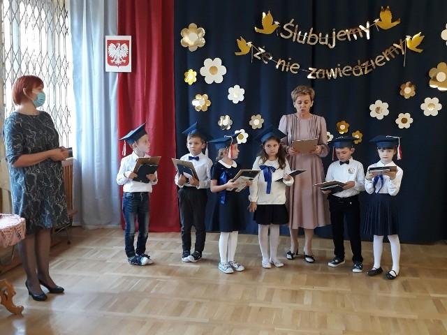Uczniowie klasy pierwszej z Publicznej Szkole Podstawowej imienia Kornela Makuszyńskiego w Młodocinie Mniejszym oficjalnie zostali włączeni do społeczności szkolnej. Uroczystość ślubowania - z racji na obecną sytuację pandemiczną - odbyła się w skromnym gronie. Zobaczcie zdjęcia z tego wydarzenia!Dzieci przygotowywały się do tej uroczystości od początku roku szkolnego pod okiem swojej wychowawczyni Idy Rogowskiej. Pierwszakom towarzyszyli rodzice i Małgorzata Tomczyk, dyrektor placówki. Uczniowie przedstawili program artystyczny, w którym zaprezentowali swoje umiejętności recytatorskie, aktorskie i wokalne. Publiczność nagrodziła dzielnych pierwszaków gromkimi brawami. Następnie w rytm poloneza przeszli do najważniejszego momentu uroczystości, którym było złożenie przez dzieci uroczystego ślubowania na sztandar szkoły, po czym, dyrektor szkoły - wielkim ołówkiem - pasowała każdego z osobna na ucznia szkoły. Ukoronowaniem aktu pasowania było wręczenie pamiątkowych dyplomów, legitymacji szkolnych, upominków od rodziców oraz odbicie śladu kciuka w kronice szkolnej. Ciepłe i miłe słowa skierowali również do pierwszoklasistów ich starsi koledzy z klasy drugiej, którzy też przygotowali dla nich niespodziankę. Na koniec dzieci odczytały i wręczyły list skierowany do Rodziców.Tradycyjnie rodzice pierwszoklasistów wręczyli dyrekcji szkoły drzewko, które będzie pamiątką tego wydarzenia. W tym roku jest to hortensja, posadzona przez wszystkich zebranych w ogrodzie szkolnym. Zwieńczeniem akademii był słodki poczęstunek przygotowany przez rodziców.