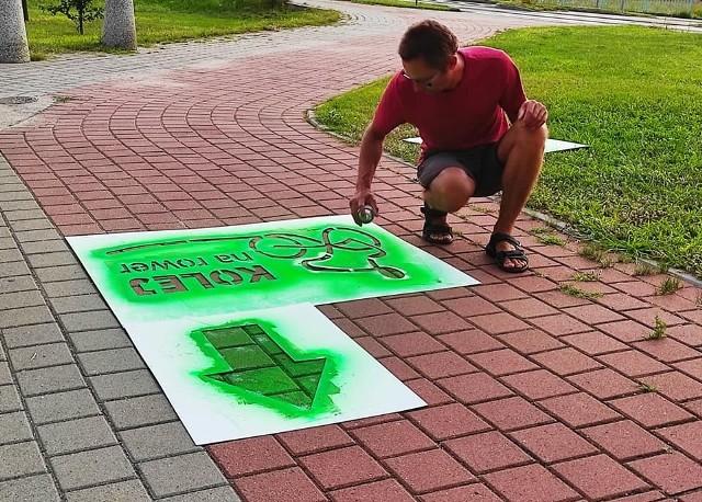 Jakub Kosiak ze Stowarzyszenia Cykliści z Soli maluje znaki, które przydadzą się zainteresowanym trasą rowrzystom.
