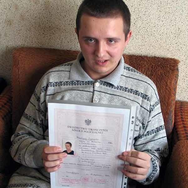 Mariusz z dumą pokazuje dyplom ukończenia studium o kierunku technik bezpieczeństwa i higieny pracy.