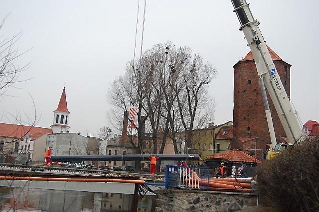 Pracownicy wodociągów starannie ukladają wielkie rury na dźwigarach noewego mostu w Brodnicy