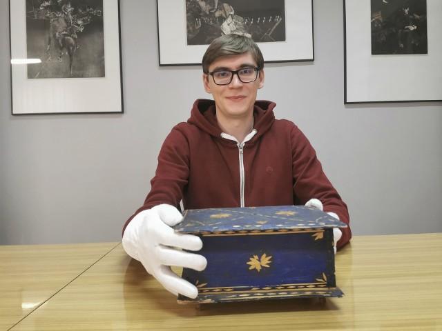 Dawid Żak prezentuje szkatułkę wykonaną przez jeńców radzieckich.