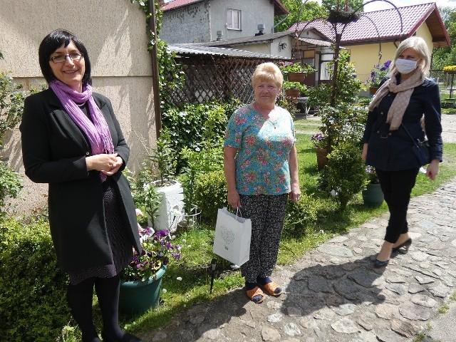 Magdalena Majewska, burmistrz Kępic (z lwej) i Marta Borodziuk, dyrektor Biblioteki Publicznej Miasta i Gminy Kępice (z prawej) wręczają upominek jednej z mieszkanek gminy uczestniczącej w akcji szycia maseczek.