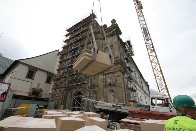 Budowa wieżyZa pomocą dźwigu na górę wciągane są kamienne element, z których składana jest wieża.
