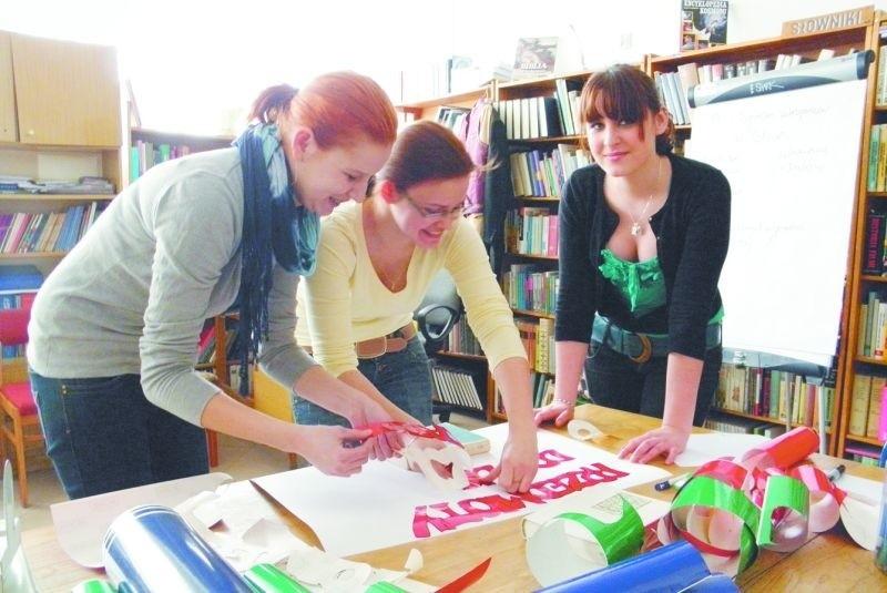 Kolorowe papiery na stole, w rękach linijki i nożyczki – Ela, Julia i Martyna w czytelni przygotowywały plakaty, które powieszą w ECK przed koncertem.