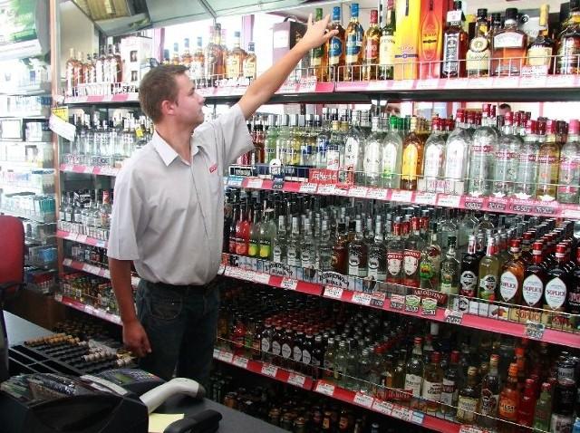 Damian Malara, pracownik stacji pali ROL–MET w Dyminach przy półce z alkoholami.