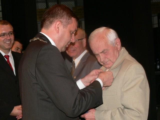 """Medal """"Sigillum Civis Virtuti"""", najwyższe odznaczenie miasta odbiera Tadeusz Wojteczko. Wręcza prezydent Grzegorz Kiełb."""