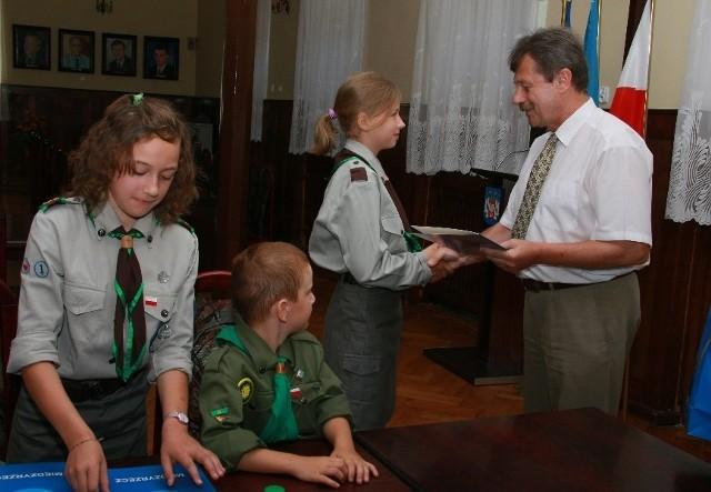Komisarz wręcza upominki Milenie Hołody, na pierwszym planie Wiktoria Śniowska i Jakub Sawicki.