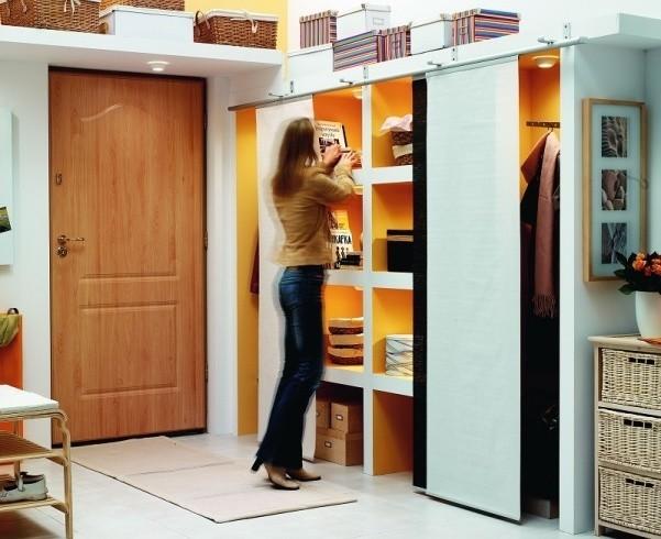 Głęboka półka nad drzwiami i przestronna szafa z zasłonami na prowadnicach pomieszczą wszystkie domowe drobiazgi.