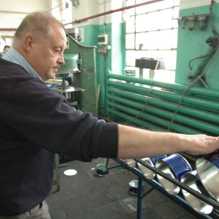Grzegorz Degut pokazuje metalowy pojemnik wyprodukowany na taśmie fabryk. - To akurat pojemnik na znicz - tłumaczy.