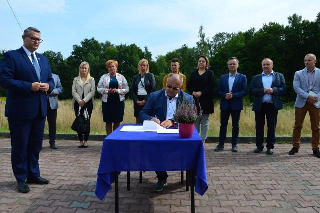 Umowę na budowę przedszkola podpisali burmistrz Myślenic Jarosław Szlachetka (z lewej) i Jan Cabak, właściciel firmy Eko-Rem-Bud (siedzi przy stole). W tle działka, a której stanie budynek