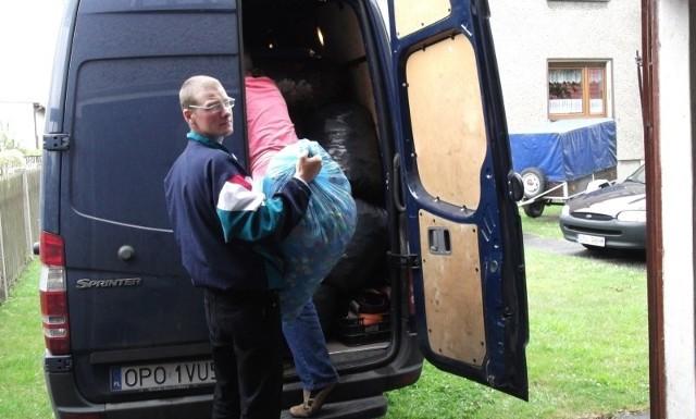 Piotr Wicher ładuje worki z nakrętkami do samochodu dostawczego