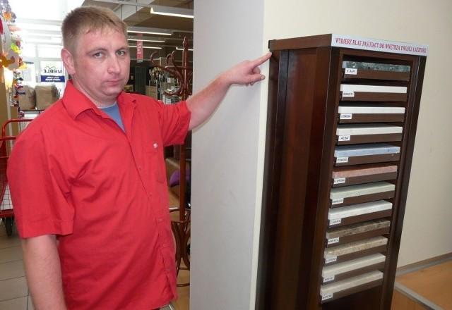 Pracownik salonu meblowego pokazuje miejsce, w którym należy przytwierdzać do ściany tego typu szafki.