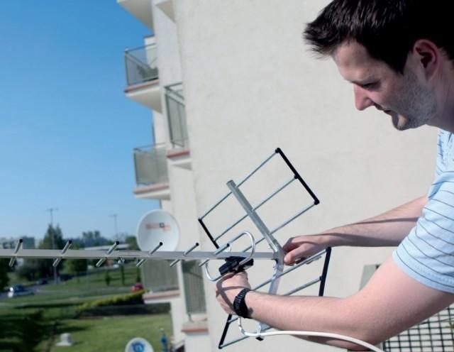 Pan Łukasz z firmy Grupa Artmedia montuje antenę do odbioru telewizji cyfrowej.