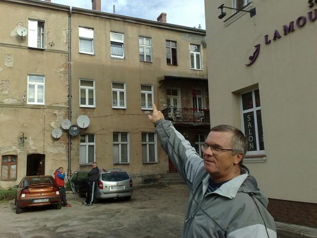 Henryk Andrałojć wskazuje na dach oficyny przy ul. Sikorskiego 25 i 25a, gdzie niedawno zrzucono pokrycie dachowe ze szkodliwego eternitu